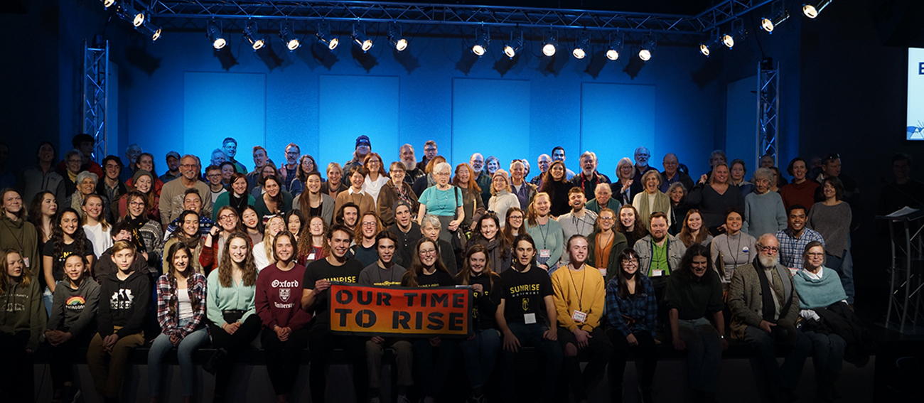 "150 people gathered for a group photo with a banner saying ""Our time to rise."""