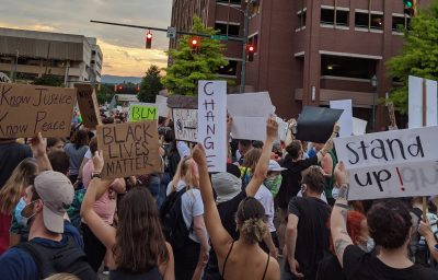 "Crowd of people in a city intersection with signs saying ""Change,"" ""Stand Up, and ""Know Justice, Know Peace"""