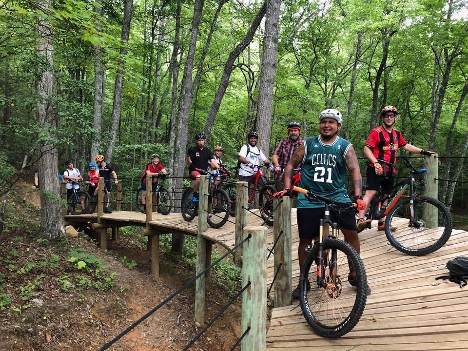 Group of riders paused on wooden ramp