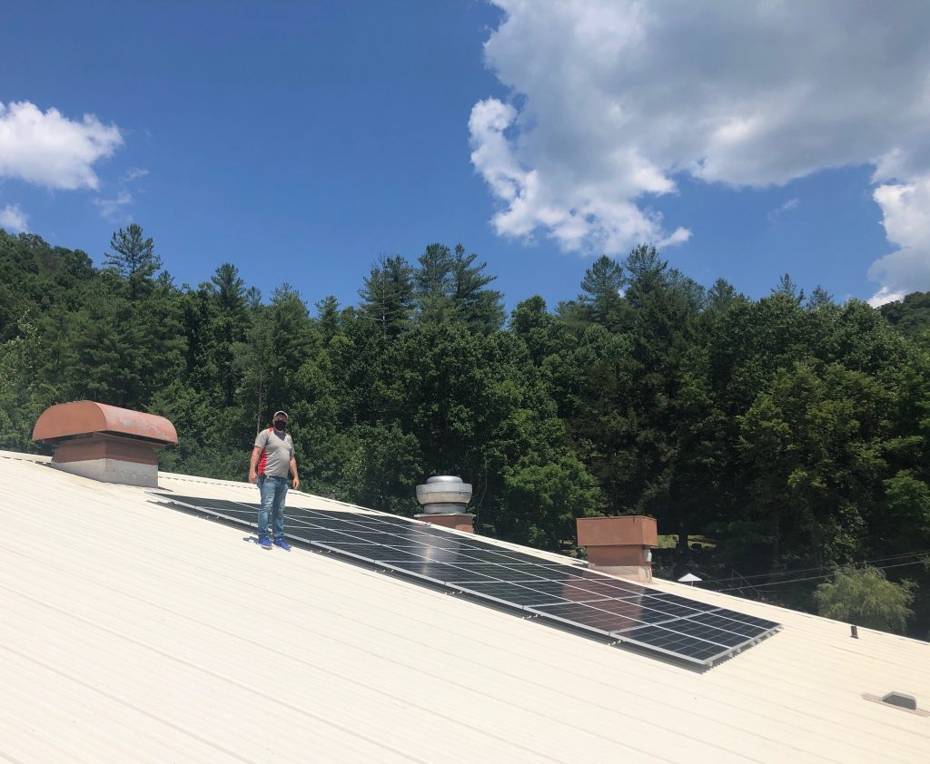 man stands roof near solar panels with trees in background