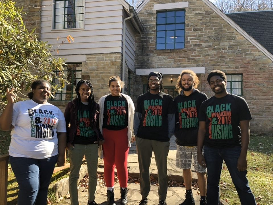 Six smiling Black young people stand in BAYR t-shirts outside in the sun