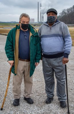 Two men in Covid face masks stand before the power plant
