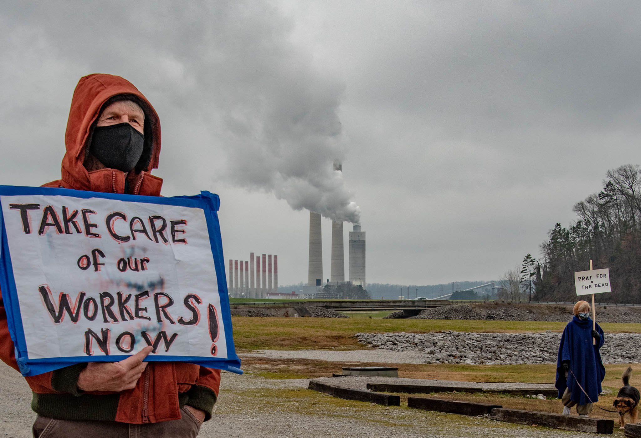 "Person holding sign saying ""Take Care of Our Workers Now"" in front of power plant"