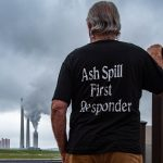 Man with gray hair facing power plant, back of shirt says Ash Spill First Responder