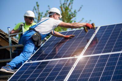 two men install solar panels