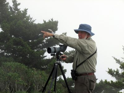 man with spotting scope points toward sky
