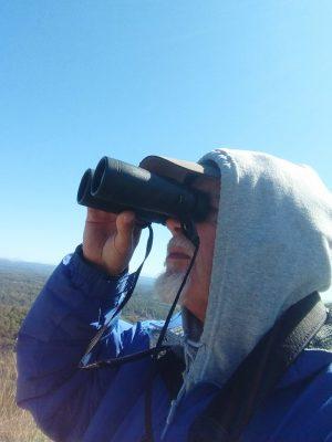 man with gray beard looks at sky with binoculars