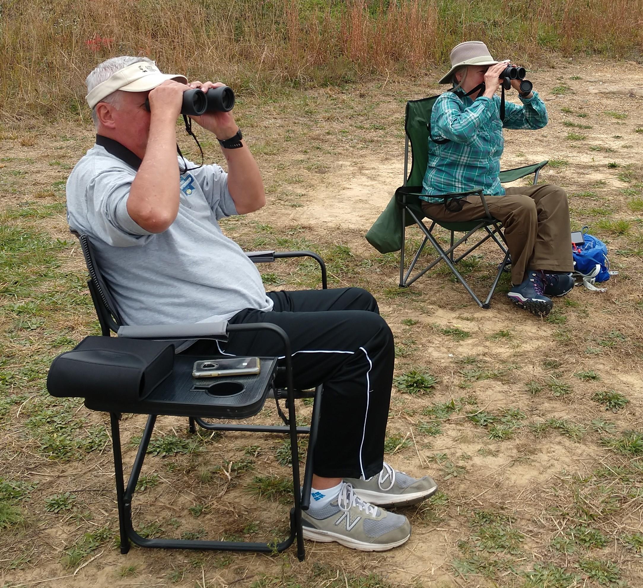 Two people seated outdoors, looking through binoculars