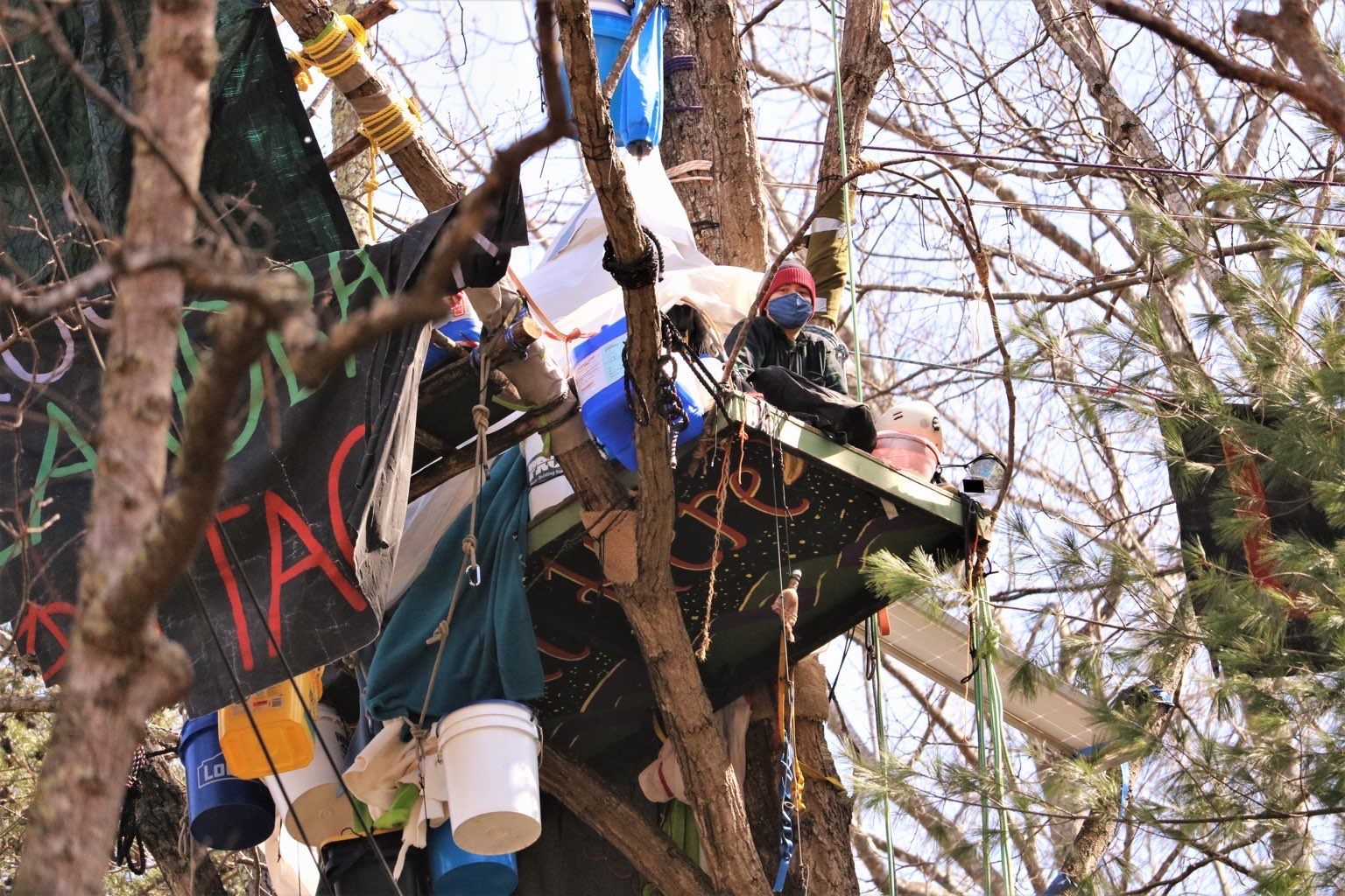person sits on a platform in a tree that is attached to banners and buckets