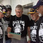 five miners wearing shirts that say Black Lung Kills gather around a notepad