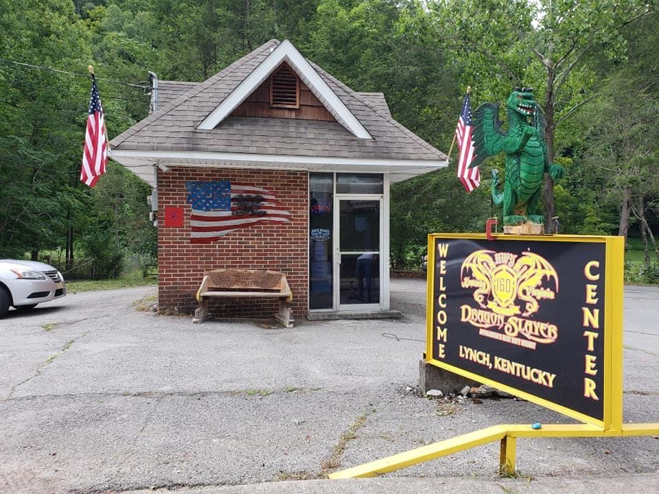 small brick building with welcome sign and American flags