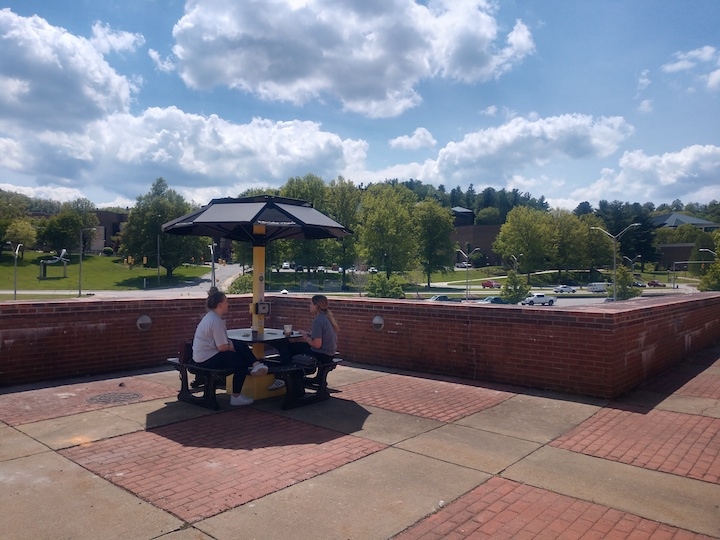 two students sit at a table with a solar panel umbrella