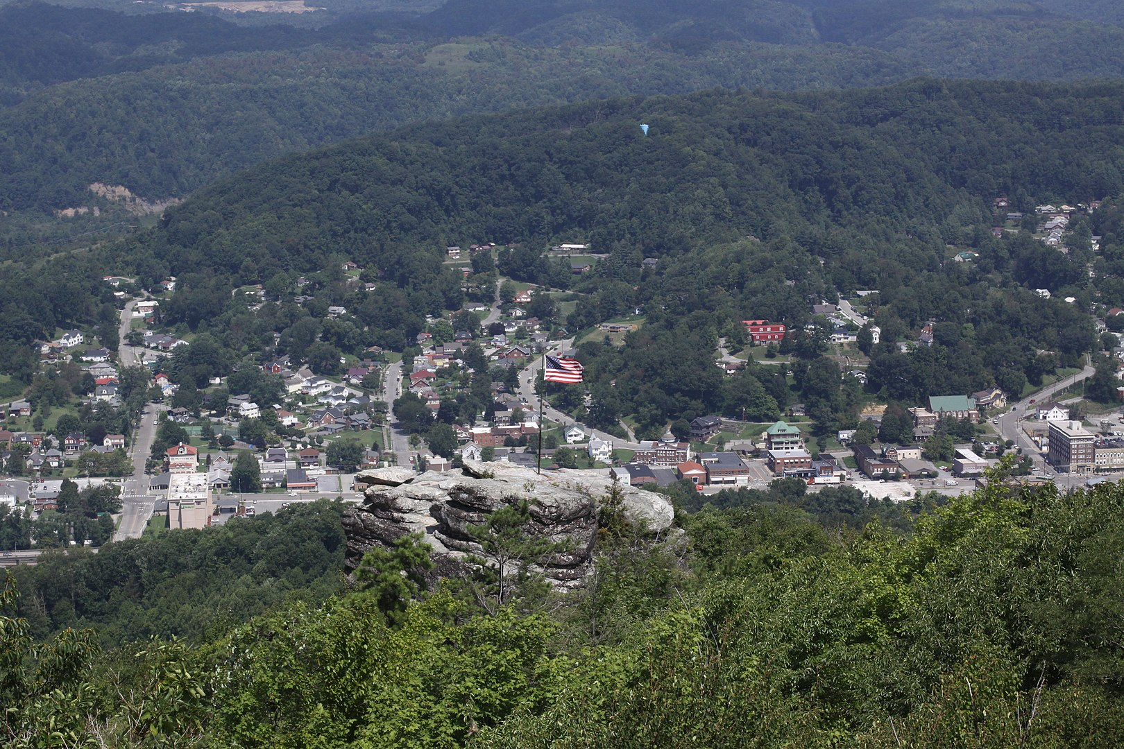 View of small town surrounded by mountains, American flag in foreground