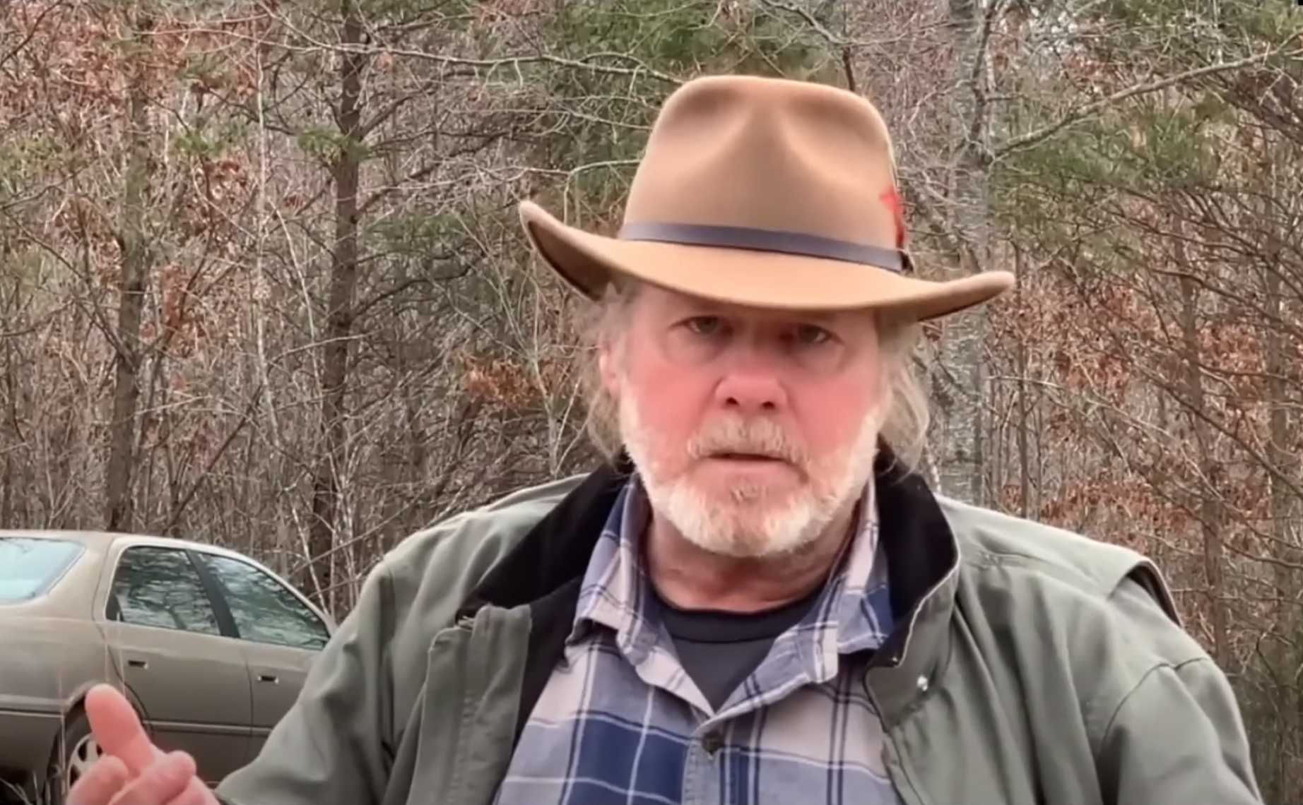 man with beard and hat speaks directly to camera