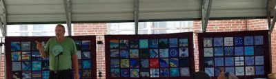 Man stands in front of row of colorful quilts