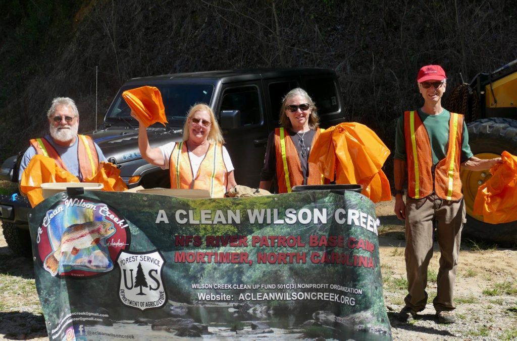 """Four participants wearing orange vests, lifting trash bags and a """"A Clean Wilson Creek"""" banner"""