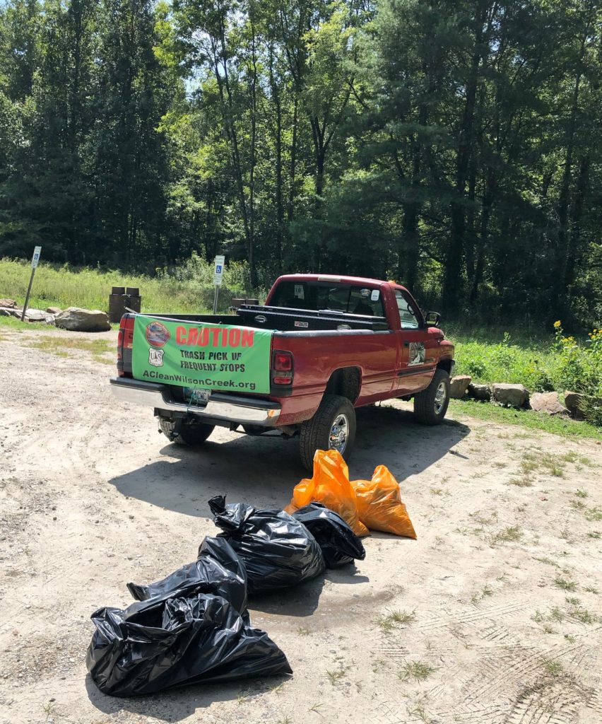 Red truck with banner explaining that the vehicle makes frequent stops to pick up trash. Several full trash bags are nearby.