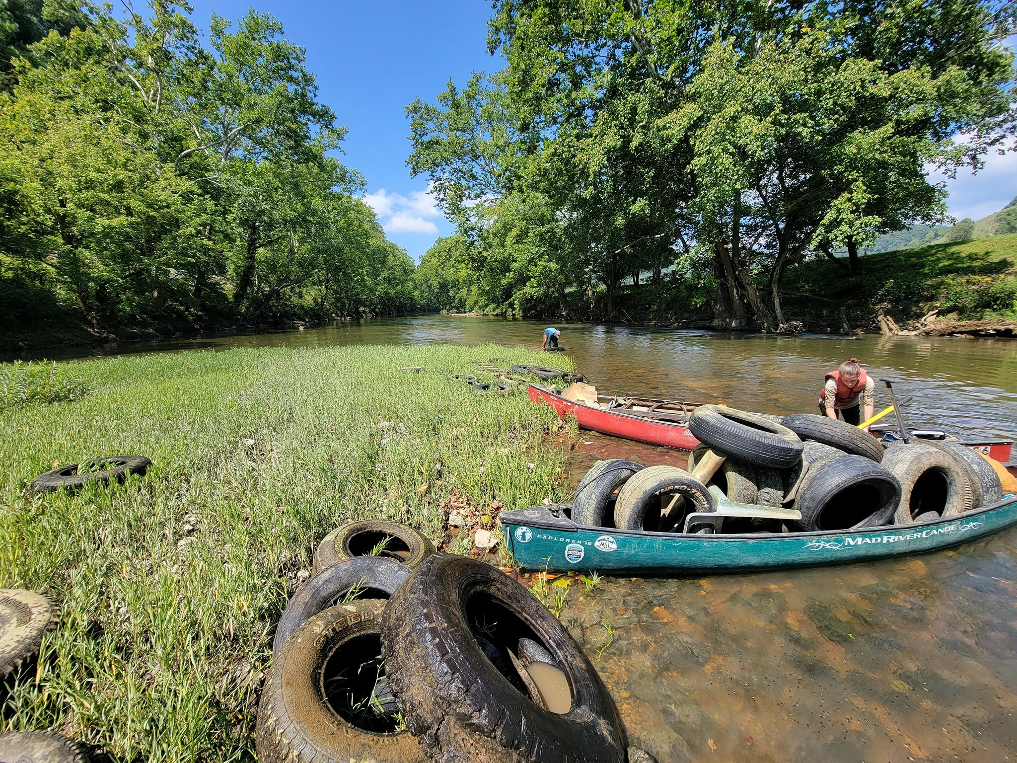 several tires lay on a low-lying gravel bar in the river and people with canoes full of tires stop to pick them up