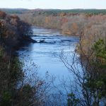 wide blue river flanked by autumn trees
