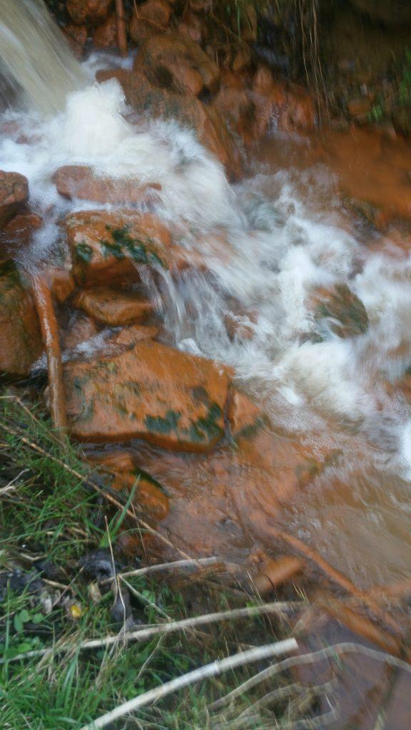 Acid mine drainage stains rocks a reddish-orange color.