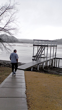 Gary Topmiller walks to the dock of his former dream home where the waters have been contaminated by toxic pollutants from the coal ash spill. Photo by Maureen Halsema.