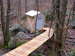 A deck leads to a shed housing a turbine and generator of Richard Cobb's microhydro system. Photo by Richard Cobb.